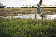 Side view of messy girl walking on wet field - CAVF16214