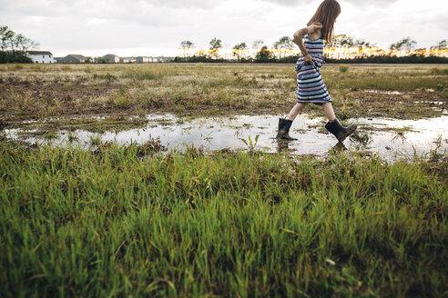 Side view of messy girl walking on wet field - CAVF16214