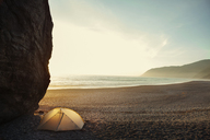 Tent by cliff on beach against clear sky during sunset - CAVF16253