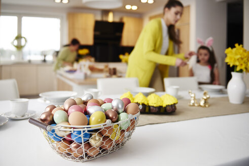 Easter eggs in basket on table at home with mother and daughter in background - ABIF00150