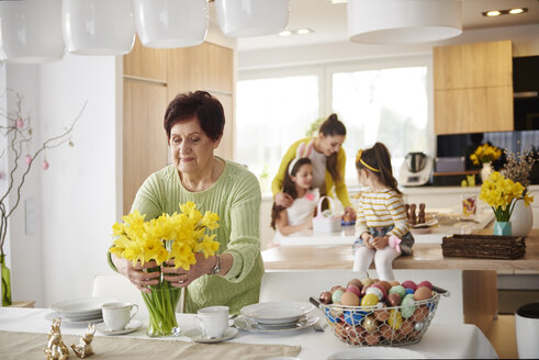 Senior woman arranging flowers on dining table with family in background - ABIF00153