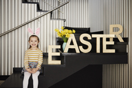 Portrait of smiling girl with bunny ears sitting on stairs next to word 'Easter' - ABIF00156