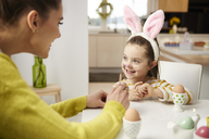 Girl with bunny ears and mother sitting at table with Easter eggs - ABIF00159
