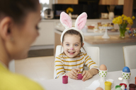 Girl with bunny ears and mother sitting at table with Easter eggs - ABIF00162