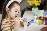 Girl with bunny ears sitting at table painting Easter eggs - ABIF00168