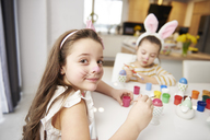 Portrait of smiling girl with sister sitting at table painting Easter eggs - ABIF00171