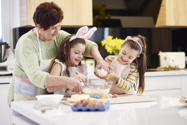 Grandmother and granddaughters baking Easter cookies in kitchen together - ABIF00180