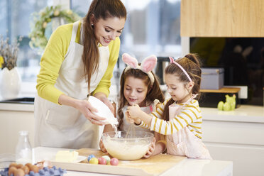 Mother and daughters baking Easter cookies in kitchen together - ABIF00183