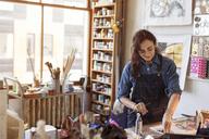 Smiling artist painting in workshop - CAVF16454