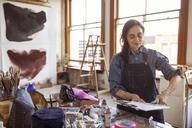 Female artist sticking glass designs on canvas at workshop - CAVF16463