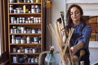 Artist holding paintbrushes in workshop - CAVF16469