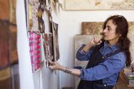 Female artist looking paintings on wall in workshop - CAVF16472