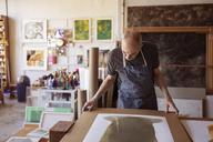 Senior artist looking painting at table in workshop - CAVF16496