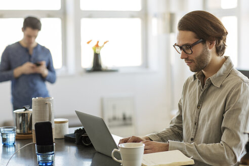 Man using laptop computer at home with boyfriend in background - CAVF16511