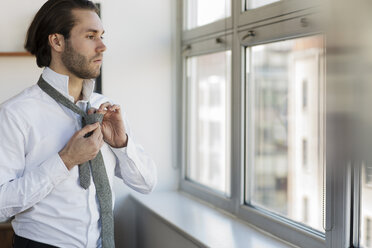 Thoughtful man looking through window tying necktie at home - CAVF16520