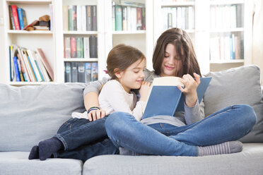 Sisters sitting on couch, reading book - LVF06811