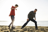 Father and son playing soccer at beach against clear sky during sunny day - CAVF16590