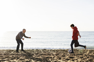 Son kicking soccer ball while father defending at beach against clear sky - CAVF16593