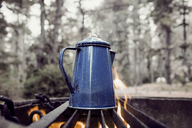 High angle view of coffee cooking on barbeque grill at campsite - CAVF16656