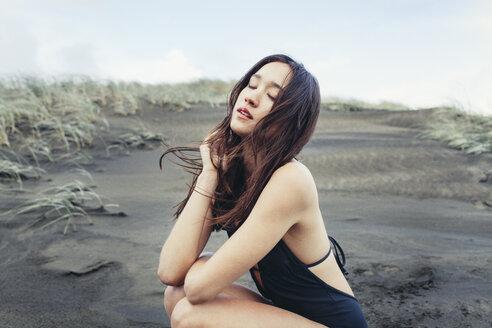 Close-up of beautiful woman crouching on wet beach - CAVF16677