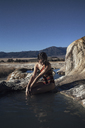 Woman sitting on rock and relaxing at Bridgeport Hot Springs - CAVF16698