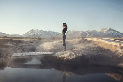 Side view of woman standing on rock at Mammoth Lake Hot Springs against clear sky - CAVF16704