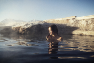 Thoughtful woman relaxing in Mammoth Lake Hot Springs against sky - CAVF16707