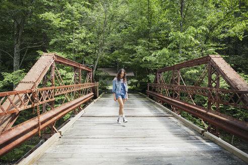 Woman walking on bridge against trees - CAVF16743