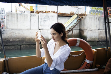 Female tourist photographing through smart phone while sitting in boat - CAVF16785
