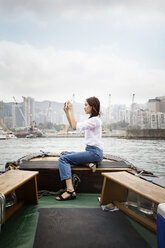 Side view of female tourist photographing while sitting on boat in city - CAVF16788