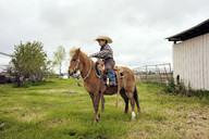 Cute cowboy riding horse on ranch - CAVF16854