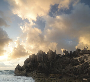 Scenic view of rock formations by sea against cloudy sky during sunset - CAVF16920