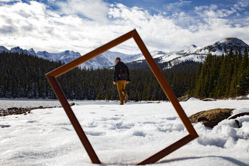 Rear view of man walking on snow covered field seen through frame - CAVF16965