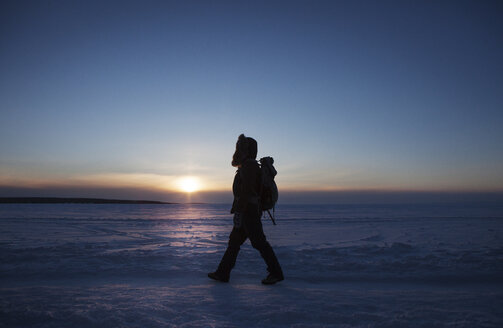 Side view of woman walking on snow covered field against sky during sunset - CAVF16986