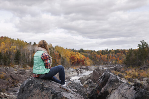 Woman sitting on rock at Jay Cooke State Park against cloudy sky - CAVF17004