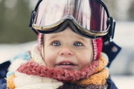 Close-up of baby girl wearing ski goggles - CAVF17049
