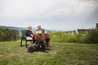 Senior couple at sitting breakfast table in lawn against sky - CAVF17160
