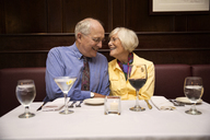 Senior couple talking while sitting in restaurant - CAVF17181
