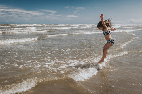 Carefree girl jumping in waves on shore at beach against sky - CAVF17310