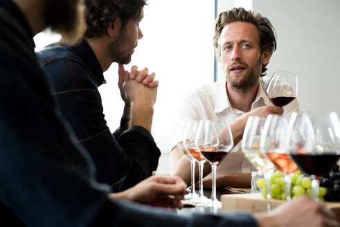 Friends talking while having wine in tasting room - CAVF17406