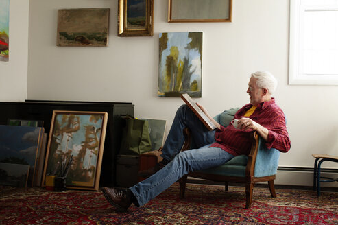 Man looking at painting while sitting on armchair - CAVF17631
