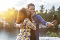 Woman kissing man taking selfie through smart phone by lake during sunset - CAVF17652