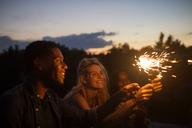 Happy friends holding illuminated sparklers at dusk - CAVF17664
