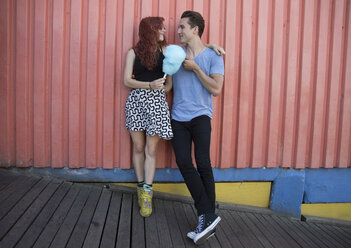 Young couple holding cotton candy while standing against wall - CAVF17670