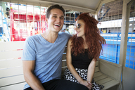Couple sitting in ride at amusement park - CAVF17673