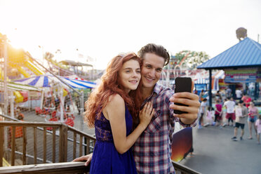 Young couple taking selfie at amusement park - CAVF17679