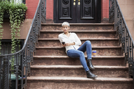 Woman using mobile phone while sitting on steps - CAVF17691
