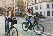Happy couple riding bicycle on city street - CAVF17748