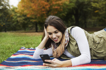 Happy woman using mobile phone while lying on blanket at park - CAVF17766