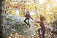 Man assisting girlfriend walking on rock in forest - CAVF17772